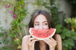 Smiling woman playing with watermelon